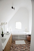 Renovated bathroom in simple attic room with terracotta floor