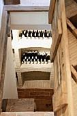 View of whitewashed brick wine racks through open cellar trapdoor