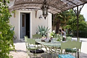 Retro-style metal chairs and table painted pale green below pergola with straw sunshade outside house with woman gardening in abckground