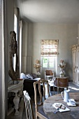 Chairs with curved backrests at rustic dining table with vintage breakfast crockery in open-plan interior with lounge area and small Rococo chairs