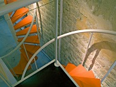 Spiral staircase with orange treads in loft apartment