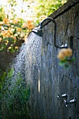 A shower on a stone wall in a garden