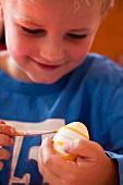 Kleiner Junge bemalt Osterei