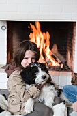 A little girl and a dog in front of a fire