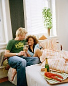 A couple having a champagne breakfast in bed
