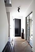 Schlichte Holzbank in modernem Flur und geöffnete Eingangstür