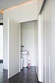 Glatte, weisse Einbaufronten und Türen zu dunklem Boden, Blick durch offene Tür auf Küchenspüle
