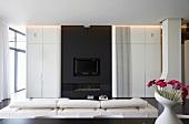 Designer-Wohnzimmer - weisse Faltwand vor schwarzer Einbaufront mit Kamin und TV