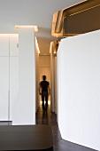 Blick in einen schmalen Gang mit dem Umriss einer gehenden Person, indirektes Licht durch entlang der Wände verlaufende Deckenschlitze