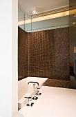 Designerbad mit gerundeter Raumecke; versenkte Wanne vor halbhoher Wand mit braun changierenden Mosaikfliesen