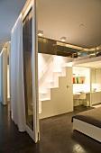 Räume im modernen Designerstil mit Glasschiebewänden und Vorhängen; Galerie mit kubischer Sambatreppe