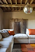 Pale sofa set and closed rough window shutters in rustic country house with spherical silver lamp hanging from wood-beamed ceiling