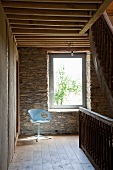 Pale blue swivel chair in sunny spot on landing next to stone wall in country house