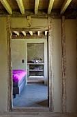 Zimmerflucht eines Fachwerkhauses durch das Schlafzimmer mit Tagesbettdecke in Magenta, in ein Bad ensuite