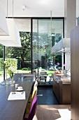 Offene Küche im Designerstil vor offener Terrassentür mit Gartenblick