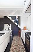 Offene Wohnküche im weissen Designerstil mit traditionell gemustertem Läufermosaik und Mann auf skulpturaler Zickzack-Treppe