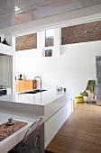 weiße Designerküche im Loft mit offenen Backstein-Elementen in der weiss verputzten Wand