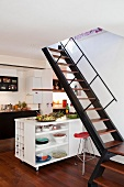 Kitchen with staircase in front of kitchen island on casters with crockery in shelving