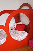 Child's bed with red, wooden, sculptural frame featuring large circular openings