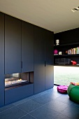 Black fitted cupboards with integrated fireplace