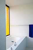 Bathtub in bathroom with mosaic tiles and yellow louver blind