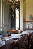 Mit Kerzenblock festlich gedeckter Tisch unter Antik-Kronleuchter in unkonventioneller Landhaus-Küche