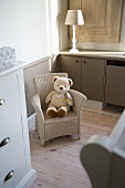 Teddy bear on child's wicker chair between turned lamp base and white, country-house chest of drawers