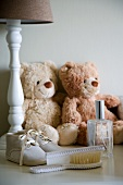 White, turned lamp base with romantic arrangement of two teddy bears, booties and ornate comb and brush set