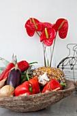 Obst und Gemüse in rustikaler Schale vor Glasvase mit tropischen Blumen
