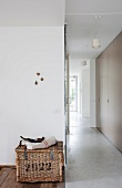 Wicker trunk in foyer and view into narrow hall with fitted cupboards