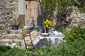 Breakfast table in garden set with yellow flowers in front of Mediterranean stone house