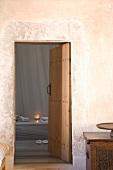 Ecke einer orientalischen Truhe und Blick durch einfache Brettertür auf Bank mit Kerzenlicht