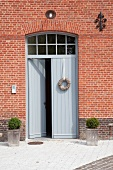 Simple, grey, double front doors in red brick facade of house