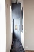 Narrow corridor with tiled floor and mirror opposite window