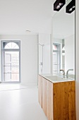 Modern, white bathroom with arched window and washstand below large mirror