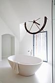 Free-standing, round bathtub below old ship's wheel in white bathroom