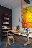 Stilmix in Raum mit Loftcharakter - rustikaler, alter Holztisch mit Dekoration und antiker Armlehnstuhl vor moderner Kunst in Gelbtönen