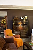 Living room in dark shades with antique wooden cabinet against brown wall and armchair with contrasting orange loose cover