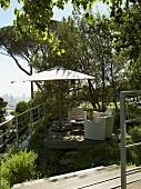 Garden furniture and parasol on wooden terrace in Mediterranean garden