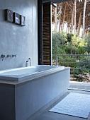 Modern bathtub in front of open terrace door with view of tropical garden