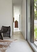 Narrow, open hallway between two rooms in minimalist, ethnic style