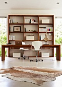 Office area flooded with light with long desk and two swivel chairs in front of open wooden shelving
