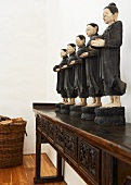 Figurines of black-clad monks on exotic console table and basket of firewood