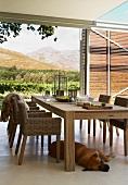 Holzstühle mit Geflecht zu handwerklich gearbeitetem, modernem Holztisch auf dem überdachtem Essplatz mit grossartigem Landschaftsblick