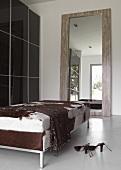 Schickes Ankleidezimmer mit dunkel glänzenden Schiebetüren am Kleiderschrank, gigantischem Spiegel und Liege mit Tierfellbezug
