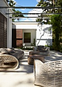 Light and shadow play on modern terrace with large but delicately crafted patio furniture and tables made from old trunks of tropical trees