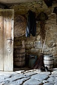 Rustic shed with stone floor and old wooden barrels against wall