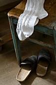 White knee socks on stool and old clogs on floor