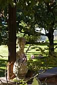 Antik griechische Steinbüste neben Metall Stütze auf niedriger Gartenmauer