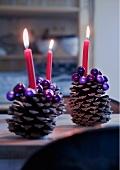 Grosse Zapfen mit lila Perlen verziert, als Kerzenständer